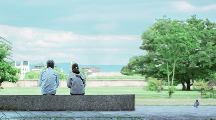 Two people sitting outside on a concrete bench in a park like setting.