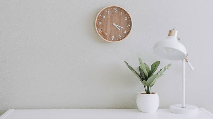 A white lamp and green plant sit on a desk, a wall clock behind them.